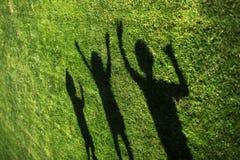 Dzieciaki z ich cieniami na trawie sylwetki trzy persons stoi z ich rękami rozciągali w górę zdjęcie stock