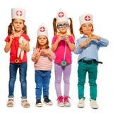 Dzieciaki z medycznymi nakrętkami i zabawki lekarki narzędziami Fotografia Royalty Free