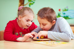 Dzieciaki z specjalnymi potrzebami rozwijają ich świetne motorowe umiejętności w daycare centrum rehabilitacji zdjęcie stock
