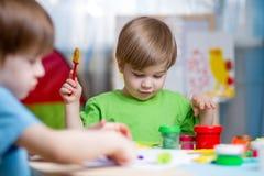 Dzieciaki z sztuki gliną w domu Fotografia Stock