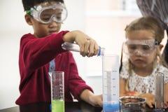 Dziecinów ucznie Miesza rozwiązanie w nauka eksperymencie Labo fotografia royalty free