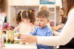 Dziecina dziecka ch?opiec budynku zabawki dom w playroom przy preschool, edukacji poj?cie obrazy stock