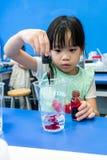 Dzieciniec dziewczyna używa kropelkę dodawać czerwonego kolor w filiżankę na b zdjęcie stock