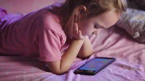 dziecka łóżko Dziewczyna przygotowywa dla spać Przed iść łóżko dziecko ogląda animowane kreskówki na zbiory wideo