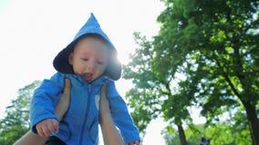 Dziecka życie bawić się w powietrzu w żywym świetle słonecznym, szczęśliwy śliczny niemowlak w błękitnym kapiszonie zbiory
