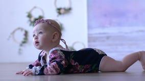 Dziecka życie kłama na podłoga i spojrzeniach w odległość indoors na unfocused tle, śliczny niemowlak zbiory