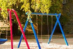 Dziecka boisko na jard aktywność parku otaczającym zielonymi drzewami przy światło słoneczne rankiem publicznie obraz stock