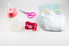 Dziecka butelka, sutek i nożyce na białym tle, zdjęcia royalty free
