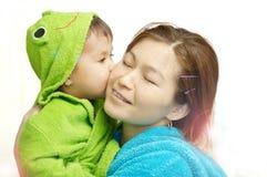 Dziecka całowania mama, szczęśliwy macierzyństwo fotografia stock