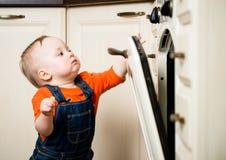 Dziecka dopatrywanie wśrodku kuchennego piekarnika Obrazy Stock