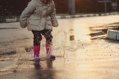 Dziecka doskakiwanie w błotnistej kałuży zbliżenie buty Fotografia Stock