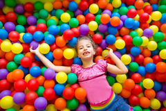 Dziecka dziewczyna na kolorowego piłek boiska wysokim widok Fotografia Stock