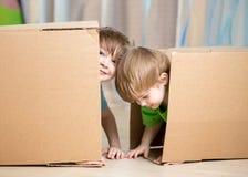 Dziecka i berbecia chłopiec bawić się w kartonach zdjęcie stock