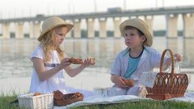Dziecka jedzenie, głodni przyjaciele chłopiec i dziewczyna w słomianych kapeluszach, jemy słodkie babeczki i napoju mleko podczas zbiory