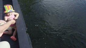 Dziecka karmienia ryba w stawie zbiory