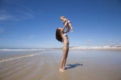 Dziecka latanie w kobiet rękach obok Conil Obraz Stock