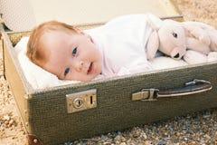 Dziecka lying on the beach w walizce Zdjęcie Royalty Free
