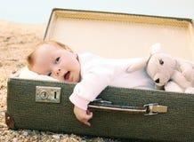 Dziecka lying on the beach w walizce Zdjęcie Stock