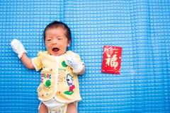 Dziecka lying on the beach z Chińską Czerwoną kopertą zdjęcia stock