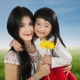 Dziecka mienia kwiat z jej rodzicem Obraz Royalty Free