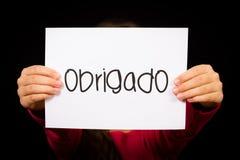 Dziecka mienia znak z Portugalskim słowem Obrigado - Dziękuje Ciebie Obrazy Royalty Free