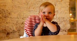 Dziecka obsiadanie na highchair klascze z rękami zdjęcie wideo