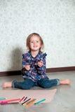Dziecka obsiadanie na podłogowym pobliskim papierze i kredkach Mała dziewczynka rysunek, obraz budynku pojęcia twórczości ręki le Obraz Royalty Free