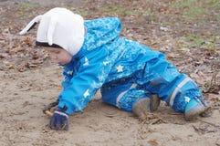 Dziecka obsiadanie na ziemi outdoors Zdjęcie Stock