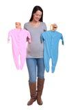 dziecka odzieżowy mienia kobieta w ciąży Fotografia Stock