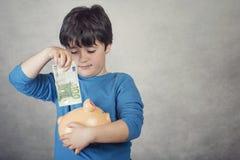 Dziecka oszczędzania pieniądze w prosiątko banku Zdjęcia Stock