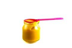 Dziecka owocowy puree w garnku z plastikową łyżką Zdjęcie Stock