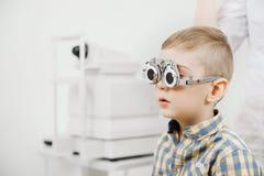 Dziecka przyjęcia lekarki oftalmolog wybiera szkła obiektyw, czeka oka widok fotografia royalty free
