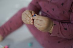 Dziecka ręka dotyka małą zabawkę z oba rękami fotografia stock