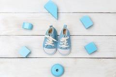 Dziecka ` s błękita buty i drewniane zabawki na białym drewnianym backgrou Obrazy Stock