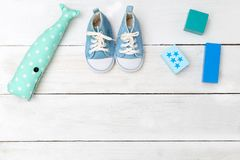 Dziecka ` s błękita zabawki na białym drewnianym tle i buty rywalizuje Obrazy Royalty Free