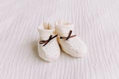 Dziecka ` s buty na białym tle Czekać dziecka biel buty dla nowonarodzonego na pastelowym błękitnym tle zdjęcia royalty free
