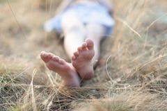 Dziecka ` s cieki w trawy dziewczyny lying on the beach na trawy relaksować Obrazy Royalty Free
