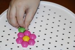 Dziecka ` s mozaika dziecko kłaść kwiatu z barwionej plastikowej mozaiki dziecka ` s ręka trzyma jaskrawego plastikowego mozaika  Obrazy Royalty Free