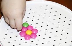 Dziecka ` s mozaika dziecko kłaść kwiatu z barwionej plastikowej mozaiki dziecka ` s ręka trzyma jaskrawego plastikowego mozaika  Fotografia Stock