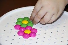 Dziecka ` s mozaika dziecko kłaść kwiatu z barwionej plastikowej mozaiki dziecka ` s ręka trzyma jaskrawego plastikowego mozaika  Zdjęcia Royalty Free