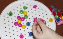 Dziecka ` s mozaika dziecko kłaść kwiatu z barwionej plastikowej mozaiki dziecka ` s ręka trzyma jaskrawego plastikowego mozaika  Obraz Royalty Free