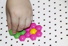 Dziecka ` s mozaika dziecko kłaść kwiatu z barwionej plastikowej mozaiki dziecka ` s ręka trzyma jaskrawego plastikowego mozaika  Zdjęcie Royalty Free