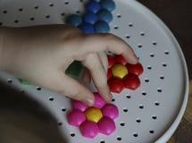 Dziecka ` s mozaika dziecko kłaść kwiatu z barwionej plastikowej mozaiki dziecka ` s ręka trzyma jaskrawego plastikowego mozaika  Zdjęcia Stock