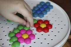 Dziecka ` s mozaika dziecko kłaść kwiatu z barwionej plastikowej mozaiki dziecka ` s ręka trzyma jaskrawego plastikowego mozaika  Obraz Stock