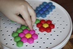 Dziecka ` s mozaika dziecko kłaść kwiatu z barwionej plastikowej mozaiki dziecka ` s ręka trzyma jaskrawego plastikowego mozaika  Obrazy Stock
