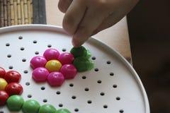 Dziecka ` s mozaika dziecko kłaść kwiatu z barwionej plastikowej mozaiki dziecka ` s ręka trzyma jaskrawego plastikowego mozaika  Fotografia Royalty Free