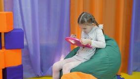 Dziecka ` s playroom Śliczna mała dziewczynka maluje na magnesowego blackboard specjalnym piórze zdjęcie wideo