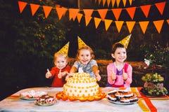 Dziecka ` s przyjęcie urodzinowe Trzy rozochoconej dziecko dziewczyny przy stołowym łasowaniem zasychają z ich mazaniem i rękami  zdjęcie stock