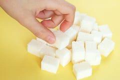 Dziecka ` s ręka bierze białego dystyngowanego cukier przypadkowo rozpraszającego na żółtym tle zdjęcia royalty free