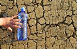 Dziecka ` s ręka dosięga butelkę wodny lying on the beach na suchej krakingowej ziemi Fotografia Royalty Free